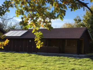 Photo of outside of toilet and shower block on campsite showing autumn leaves and solar panels