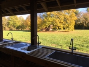 Photo looking out from washing up area to campsite in autumn colours
