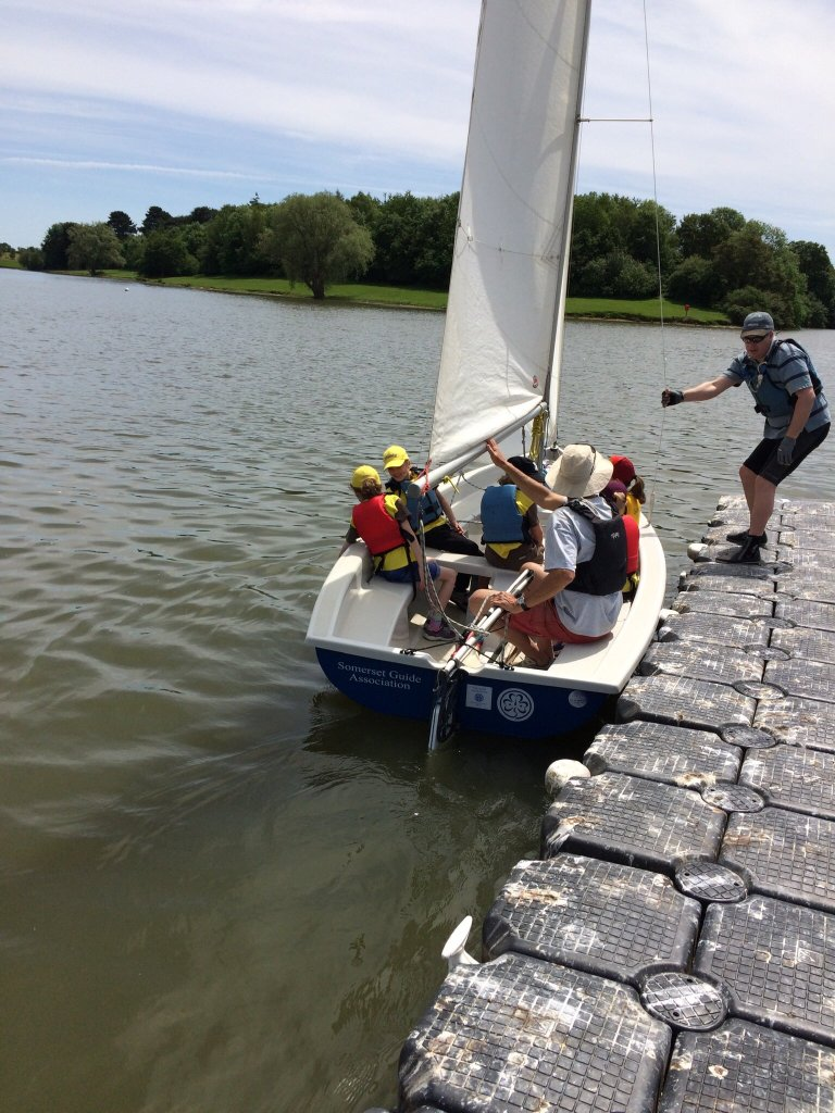 Photo of Ash on the pontoon assisting Paul and some Brownies as they set sail on Somerspirit