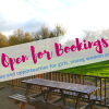 Photo from Somermead decking / picnic benches looking out over green space with banner indicating 'Open for Bookings: outdoor venue and opportunities for girls, young women and their families